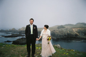 a beautiful bride looks at her husband as she holds her colorful bouquet on the rugged rocky cliffs of sonoma coast northern california shot on a holga using fuji pro 400 h 120 film