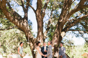 a bride and groom at their ceremony hold hands and say their vows under a giant oak tree at val du vino winery in murphys, ca