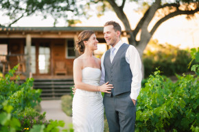 a happy bride and groom hold each other amidst the vineyards of still waters winery in paso robles, ca