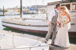 a happy groom kisses his laughing bride on her head surrounded by old boats in bodega bay harbor at the compass rose gardens