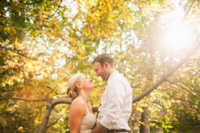 happy couple bride and groom laugh under bright beautiful fall color leaves at sunset at their backyard wedding