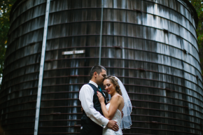 happy couple newlyweds bride and groom hug in the santa cruz mountains among the redwoods in front of a wood water tower at the sequoia retreat center wedding in ben lomond, ca