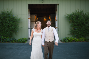 happy couple holds hand after their ceremony bride and groom walk together at bargetto winery in soquel while laughing