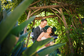 happy couple bride and groom hug each other in a lush garden setting under a wooden arbor smiling and laughing at their wildwood acres wedding before their intimate ceremony
