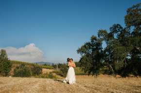 happy couple hugging in an open field on a clear blue sky day with the rimfire wild fire in the background with smoke plumes in the distance at their wedding after their ceremony at sierra glen apple ranch in sonora tuolumne county