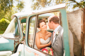 happy couple bride and groom sit in an old pickup at their oak farm vineyards wedding in lodi ca