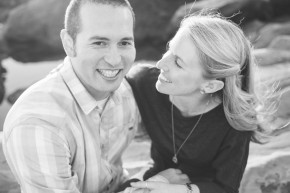 black and white image happy smiling newly engaged couple smile for the camera on the beach in point lobos state park monterey carmel, ca