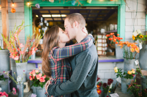 a happy newly engaged couple take their engagement session portraits at the flower shop in santa cruz, ca and kiss hugging for the camera