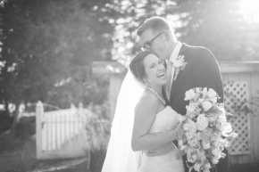 black and white image of a happy couple kisses and laughs bride and groom celebrate their highlands park wedding in ben lomond, ca reception santa cruz wedding photographer