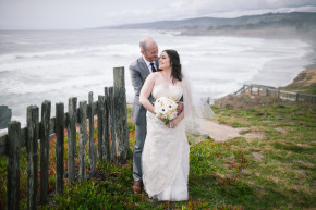 happy couple bride and groom hug and hold each other on the coastal cliffs of northern california sonoma coast at their sea ranch wedding elopement