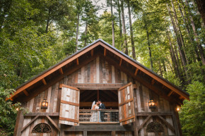 bride and groom kiss in the barn amidst the tall trees in the green redwood forest in the santa cruz mountains at their stones & flowers wedding