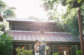 happy couple newlyweds bride and groom huge and kiss under some strung lighting in front of a beautiful rustic chapel barn during sunset showing sun flare coming off the camera lens at their rustic barn union hill inn wedding in sonora columbia, ca