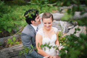 happy bride and groom sit and hug and hold eachother and nuzzle in her veil among the green trees and leaves on their beautiful summer quail hollow wedding in felton, ca wedding venue