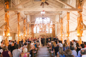 brenizer image of happy newlywed couple bride and groom exchanging rings during their ceremony in a gorgeous whitewash chaple with twinkle lights at their beautiful union hill inn wedding in sonora, ca on a beautiful summer day