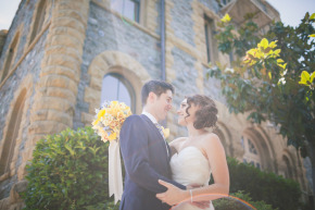 a young happy newlywed couple on their sunny wedding day hold each other bride holding her bouquet with her groom in front of an old stone building with sun flare coming through the green trees at their san francisco theological seminary wedding