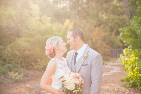 happy couple newlyweds dressed in their wedding gown and grey suit hold her bouquet hugging and kiss for the camera in the sunset light during a beautiful fall evening golden hour at their monte verde inn wedding in foresthill, ca outside of auburn