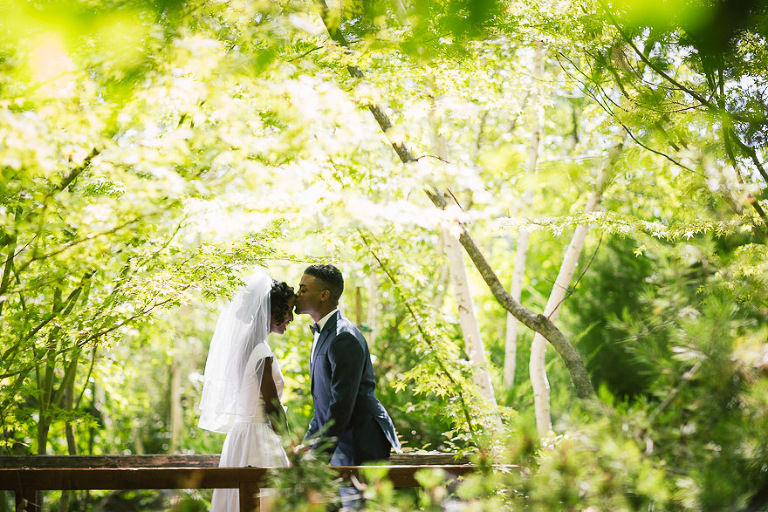 happy african american black jamaican couple get married hold hands and kiss in their wedding gown and veil mensware suit and tie on a wooden bridge among the green trees at their ironstone winery wedding in murphys in california gold country