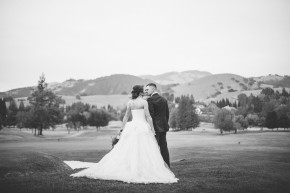 black and white photograph of a happy newlywed couple bride in her beautiful white bridal gown wedding dress holding her floral bouquet of flowers and groom in his tuxedo bowtie hold hands and kiss on the golf course of the 5th hole with mount diablo in the background after their ceremony at their diablo country club wedding reception at sunset