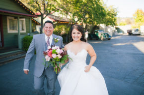 happy bride and groom hold hands and walk and smile at the camera with white wedding gown dress floral bouquet happily laugh at their bargetto wedding soquel winery wedding in santa cruz ca
