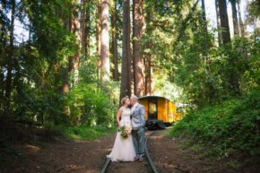 happy newlyweds bride in her white wedding gown dress holding her floral bouquet and groom in his mens suit hold each other and kiss for the camera amongst the tall green redwoods during mid summer on the railroad tracks at their roaring camp wedding