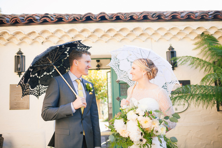 happy couple bride in her white wedding dress gown holding her gorgeous floral bouquet of flowers and groom in his sharp grooms suit hold their new orleans style umbrellas in front of the allied arts guild wedding the perfect menlo park wedding venue the perfect silicon valley wedding venue