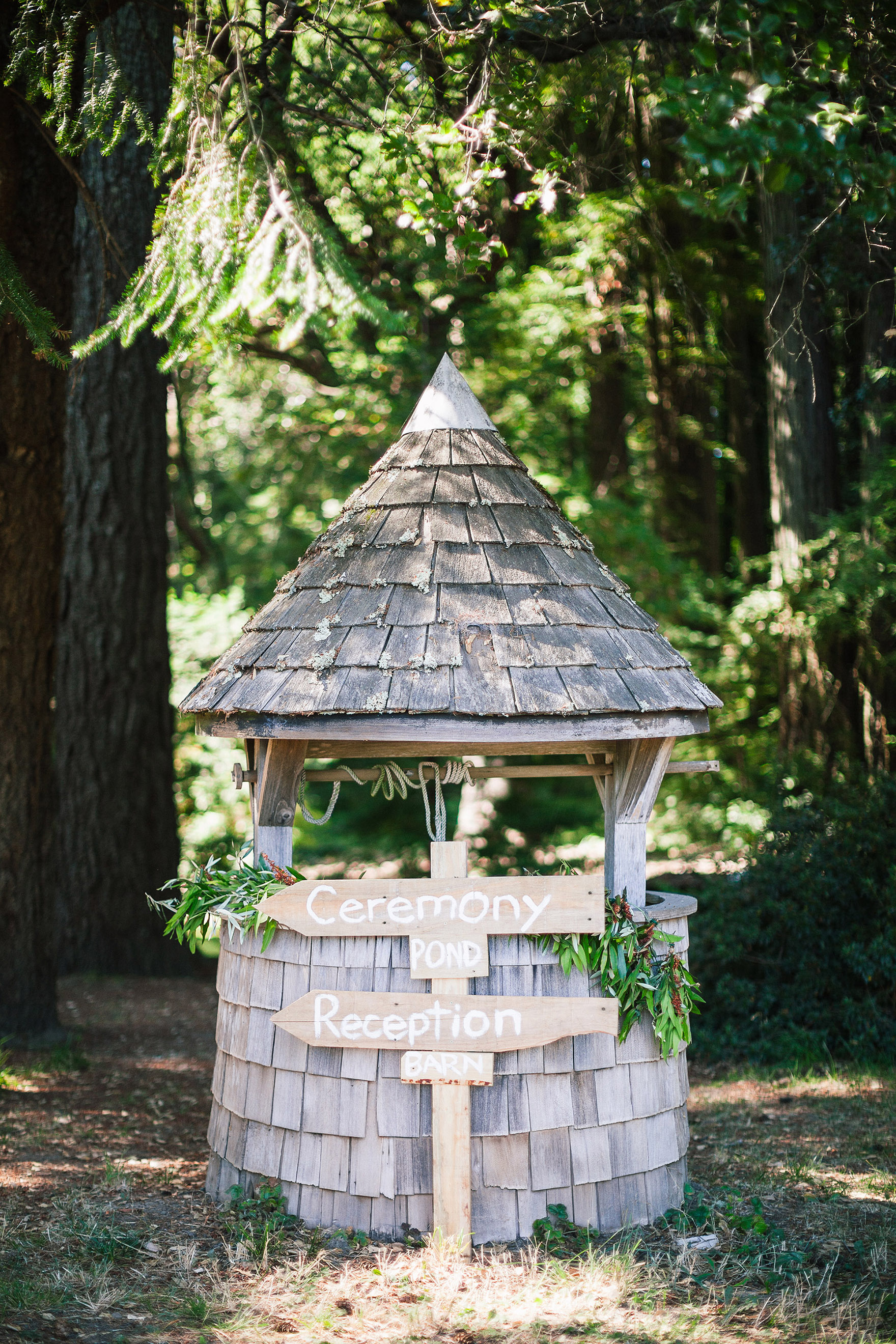 detail shot of an old vintage well and hand painted diy signs signage for this amazing redwood estate wedding the perfect los gatos wedding venue in the santa cruz redwood mountains