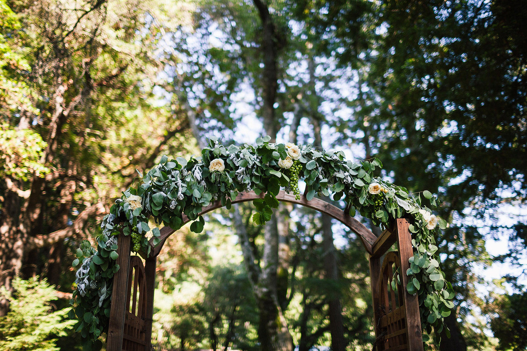 flowers decorate this archway arbor where bride and groom stand during their redwood ridge ceremony saying vows and first kiss among the tall redwoods redwood ridge estate wedding the perfect los gatos wedding venue santa cruz wedding venue