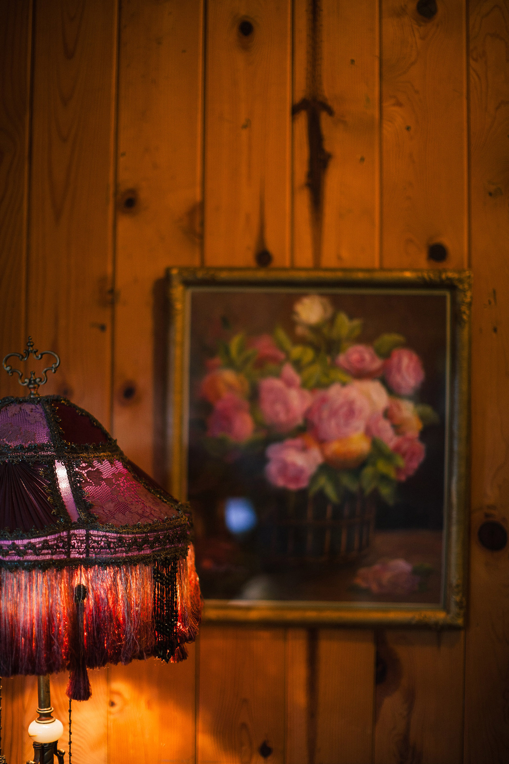 vintage antique lamp framed by a floral painting flowers on a wood paneled wall in the cottage on the property redwood ridge estate wedding redwood ridge wedding the perfect santa cruz wedding venue los gatos wedding venue