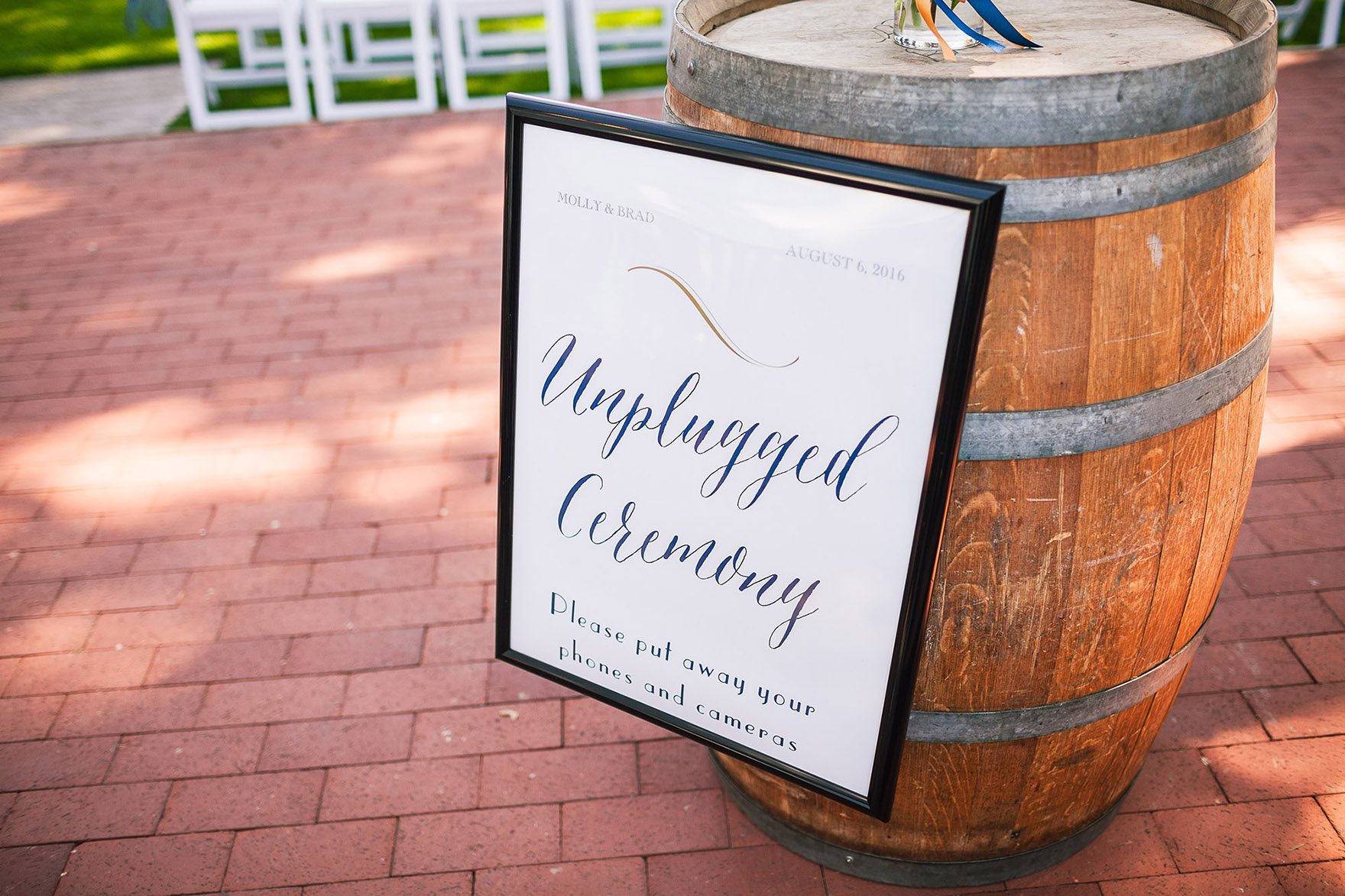 unplugged wedding signage sign asks guests no cellphones please enjoy the ceremony posted on the wine barrel on the bricks down the aisle at the pasatiempo golf course at the bride and groom newlywed hollins house wedding the perfect santa cruz wedding venue