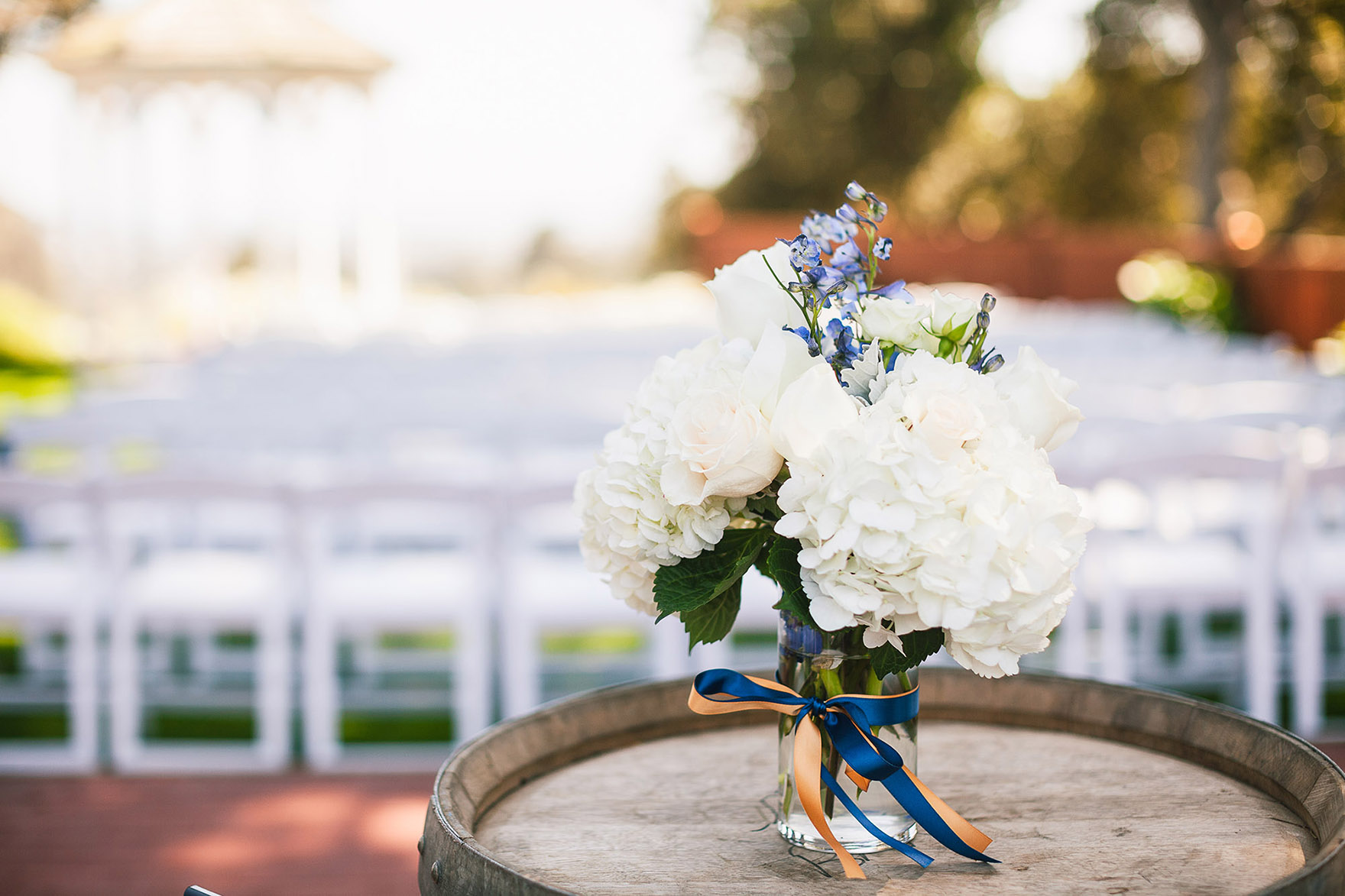 bouquet vase of flowers sits on a wooden wine barrel decor decorations diy ready for the ceremony down the aisle at the pasatiempo golf course at the bride and groom newlywed hollins house wedding the perfect santa cruz wedding venue