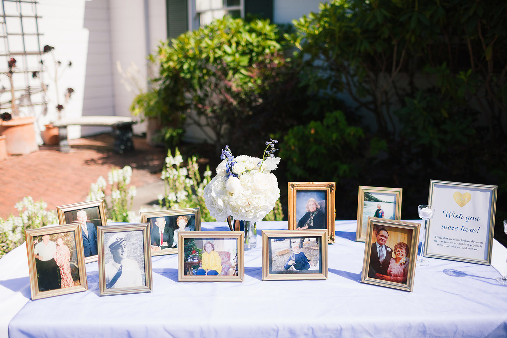 arrangement of picture frames and vases with flowers decorate a welcome table at the pasatiempo golf course at the bride and groom newlywed hollins house wedding the perfect santa cruz wedding venue