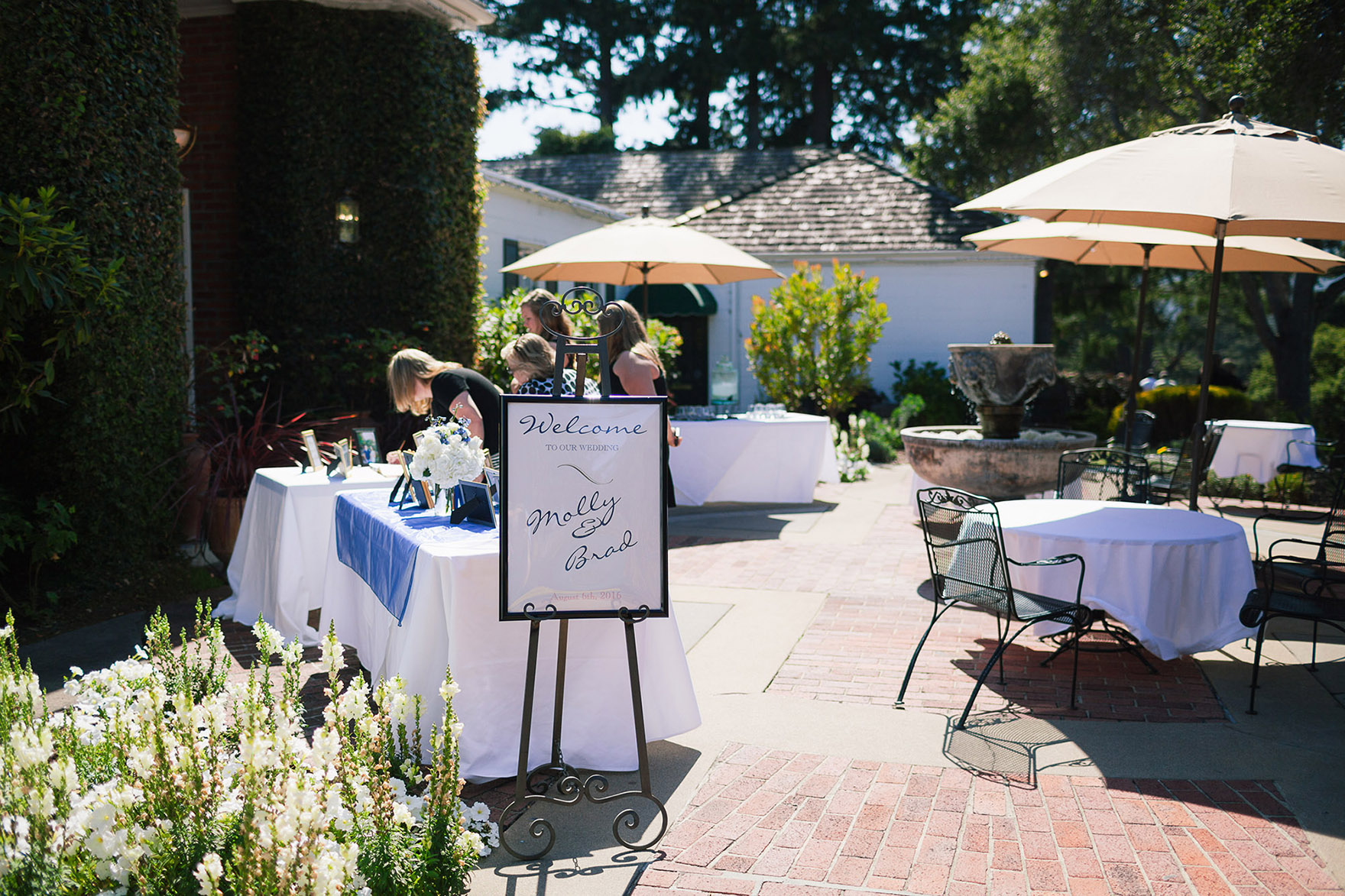 welcome sign greets visitors and family while guests sign the welcome album guestbook on the patio at the front of at the pasatiempo golf course at the bride and groom newlywed hollins house wedding the perfect santa cruz wedding venue
