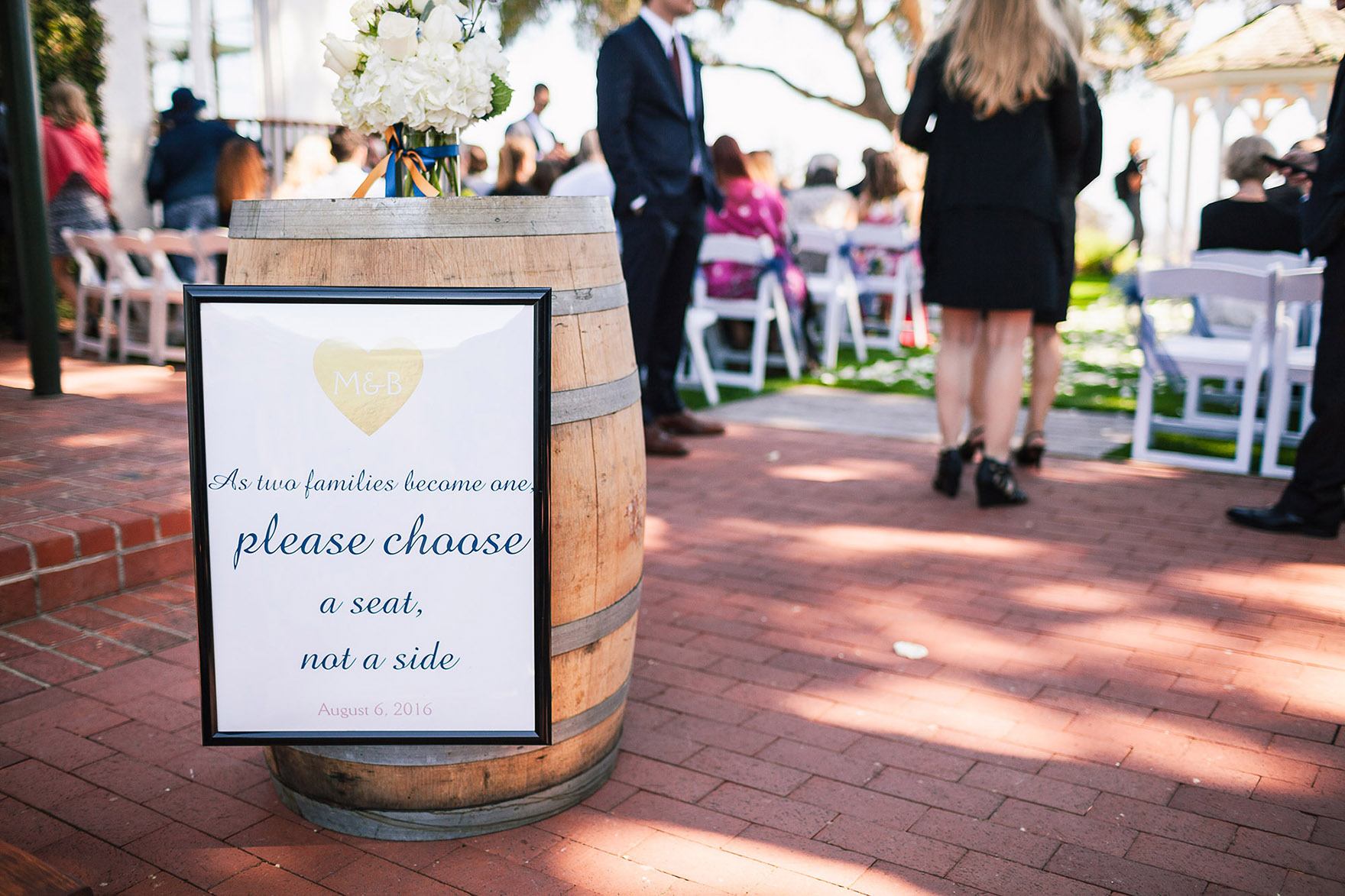 signs signage greet wedding guests and family and friends framed on the wine barrel sitting on the brick as people wait for the ceremony to start at the pasatiempo golf course at the bride and groom newlywed hollins house wedding the perfect santa cruz wedding venue