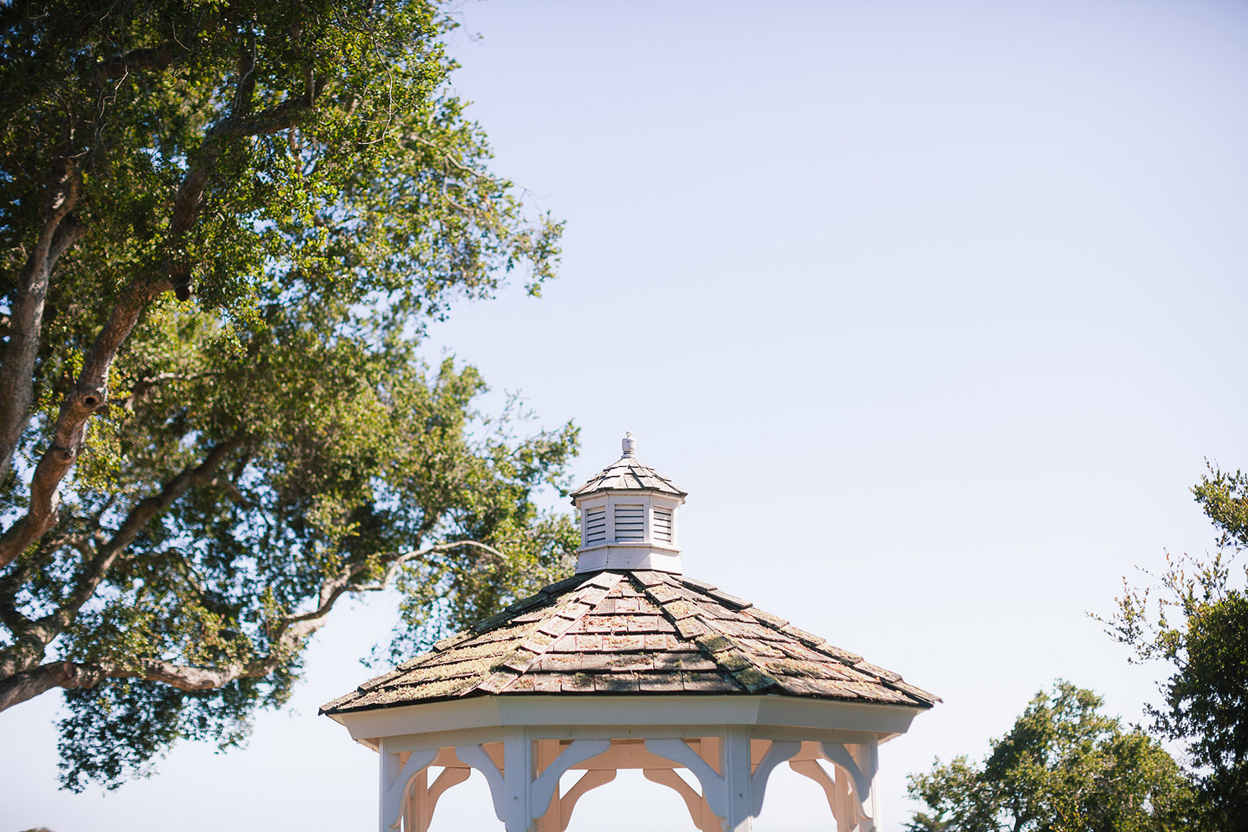 blue sky skies and tall oak trees frame a gazebo at the ceremony site at the pasatiempo golf course at the bride and groom newlywed hollins house wedding the perfect santa cruz wedding venue