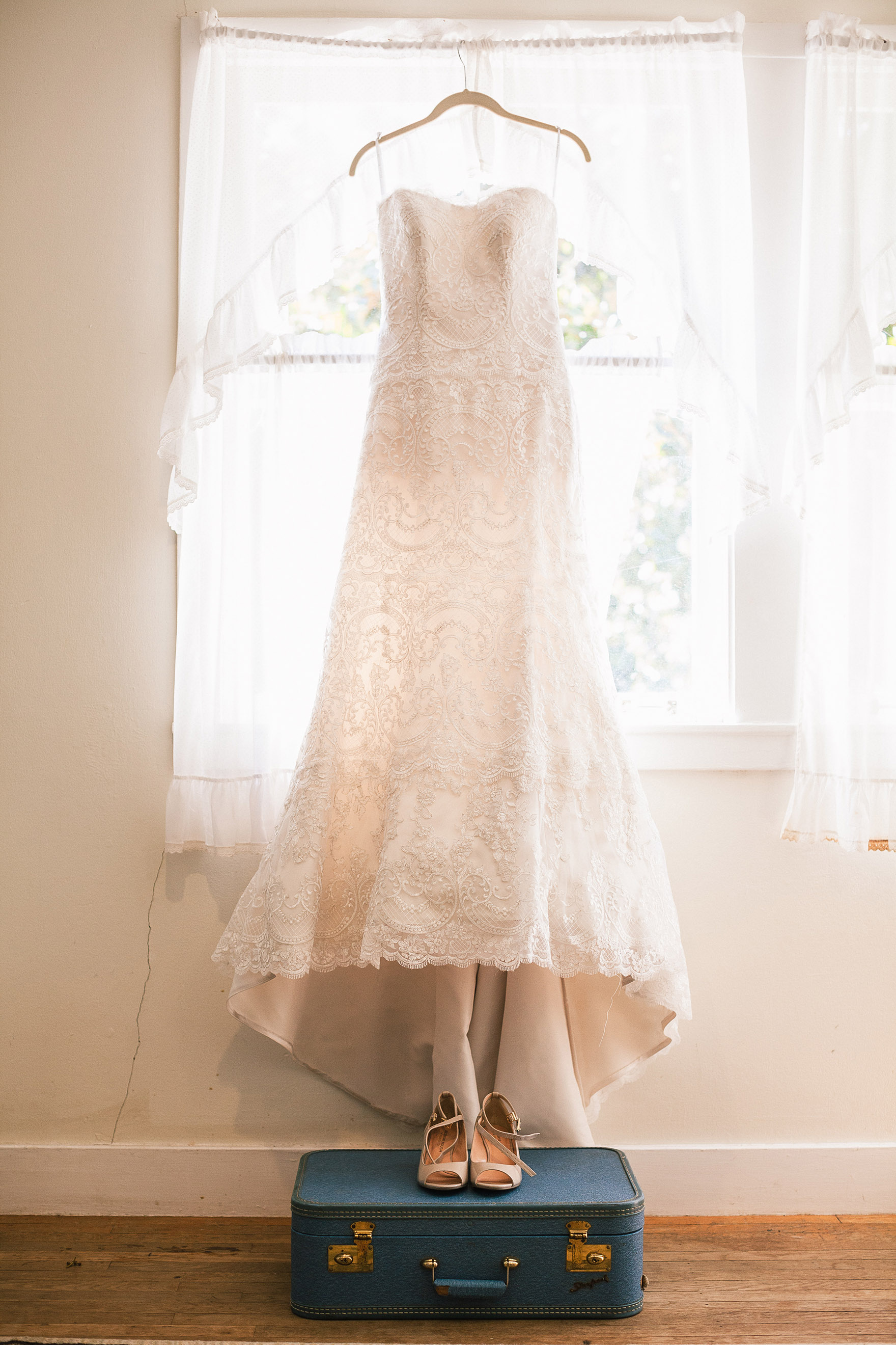 beautiful elegant white wedding dress gown hangs in the window of the cottage inside at a highlands park wedding the perfect felton wedding venue santa cruz wedding venue redwood wedding venue santa cruz wedding photographer