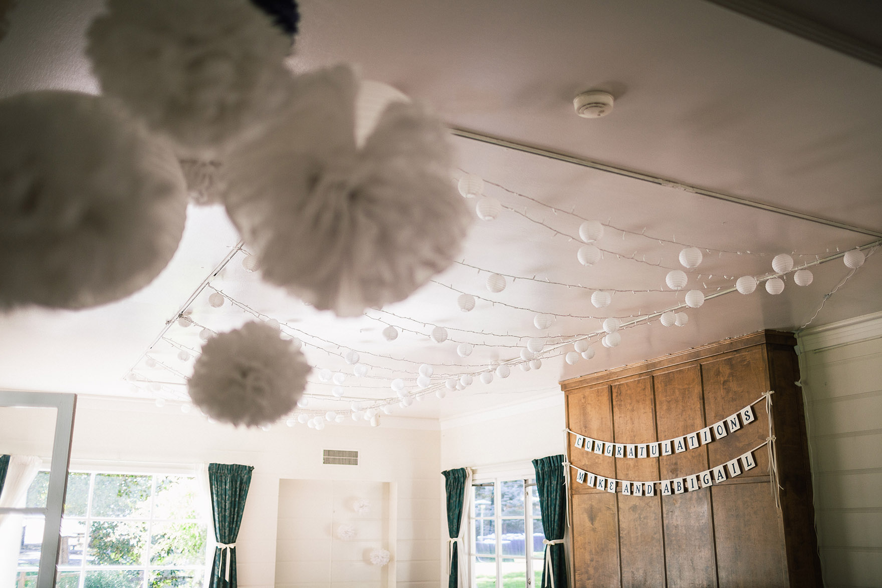 string lights twinkle dangle from the white ceiling inside the home cottage house at a highlands park wedding the perfect felton wedding venue santa cruz wedding venue redwood wedding venue santa cruz wedding photographer