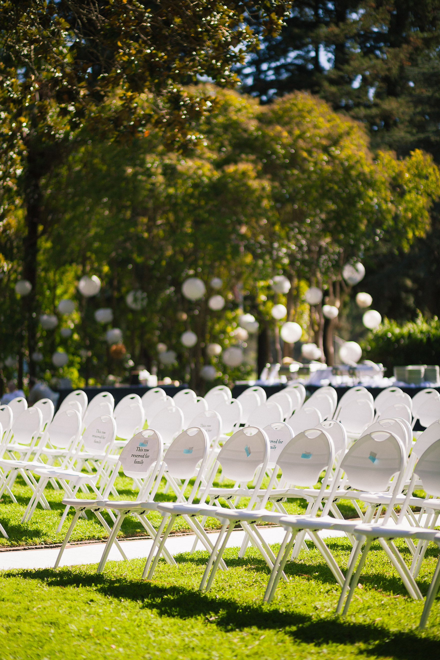outdoors in the summer sun the guest seating seats chairs wait for the highlands park ceremony to start begin in the green fields grass lawn at a highlands park wedding the perfect felton wedding venue santa cruz wedding venue redwood wedding venue santa cruz wedding photographer