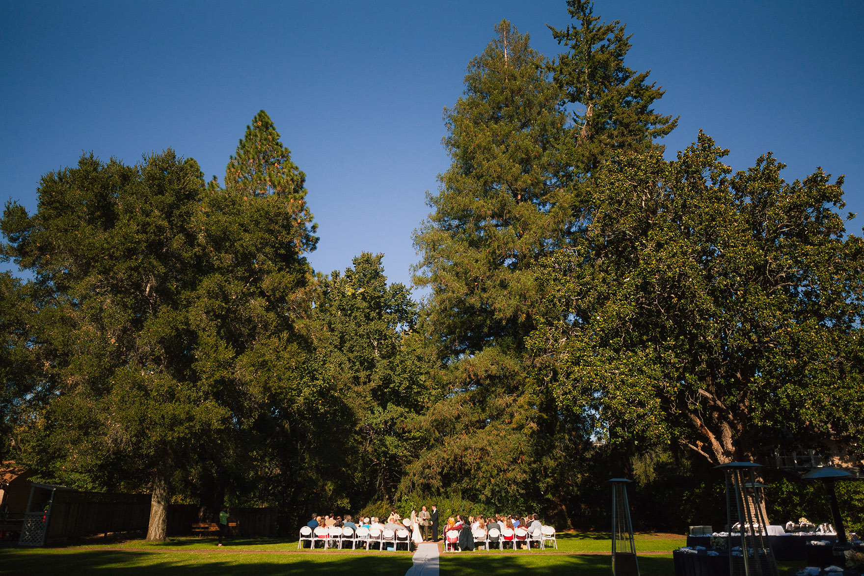 highlands park wedding ceremony takes place under the summer sun under the tall pine tree redwoods in the green open field lawn grass table settings blue table cloth white globe lights dangle from green lush trees with floral center pieces flowers waiting for the highlands park wedding reception to begin start at a highlands park wedding the perfect felton wedding venue santa cruz wedding venue redwood wedding venue santa cruz wedding photographer