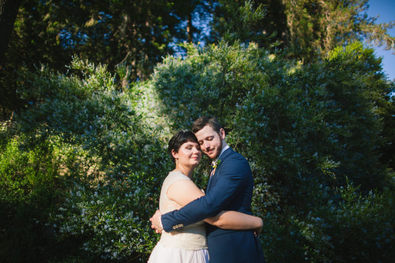 happy couple newlyweds bride and groom hold each other hugging after their pema osel ling ceremony light shines on their smiling faces posed in front of spring blooming tree at amphitheatre of the redwoods wedding shot by jeremy from still music local Monterey Bay Wedding Photographer