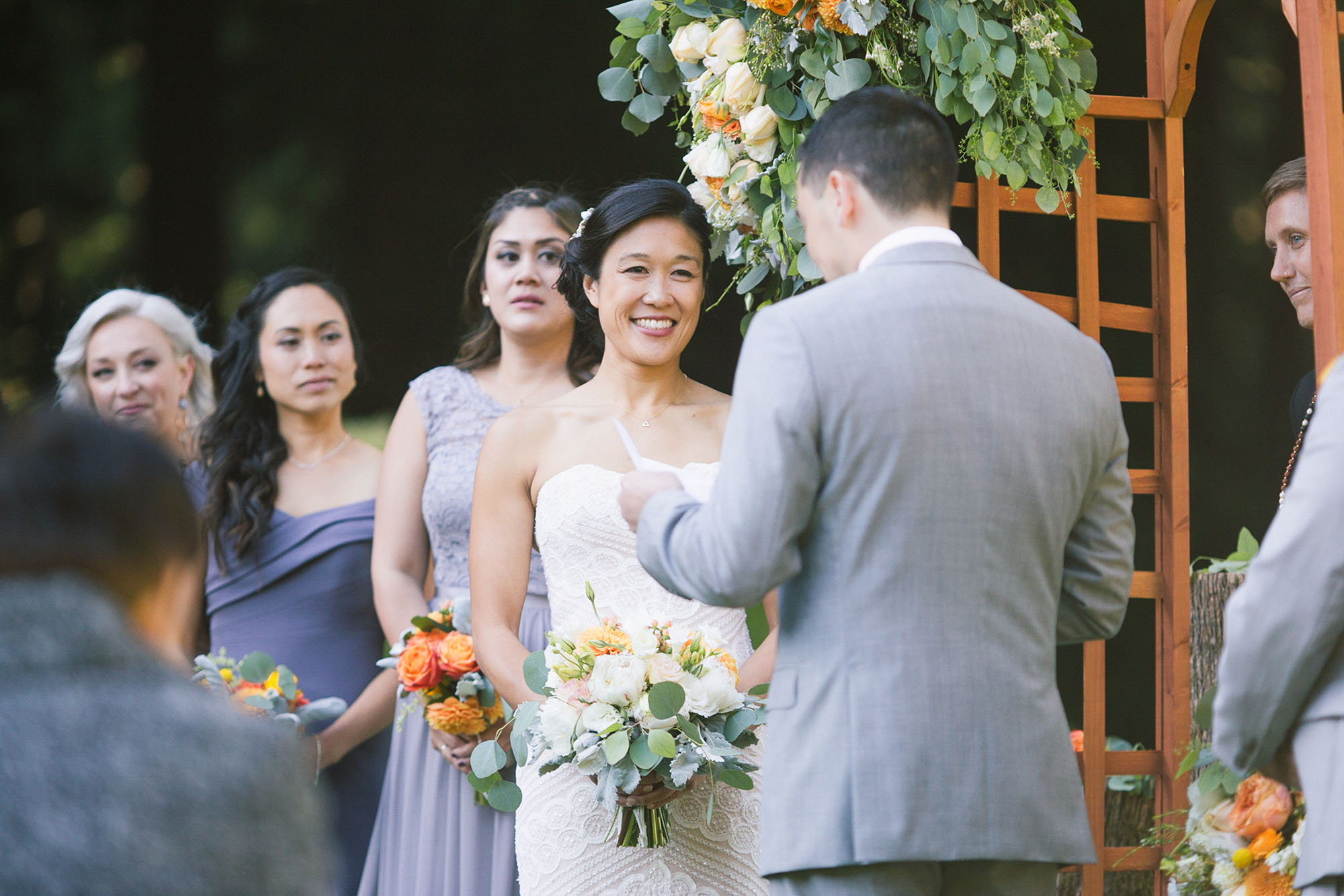 happy bride in her white dress smiles at her handsome groom reading his wedding vows during their ceremony celebration at their mountain terrace wedding in the santa cruz mountains los gatos hills palo alto hills