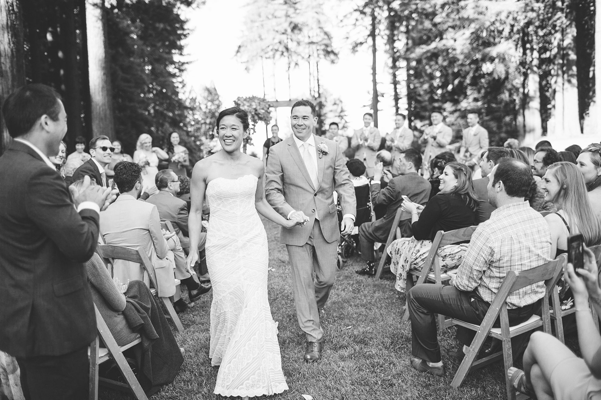black and white image of bride and groom walking down the aisle after their ceremony celebration at their mountain terrace wedding in the palo alto hills