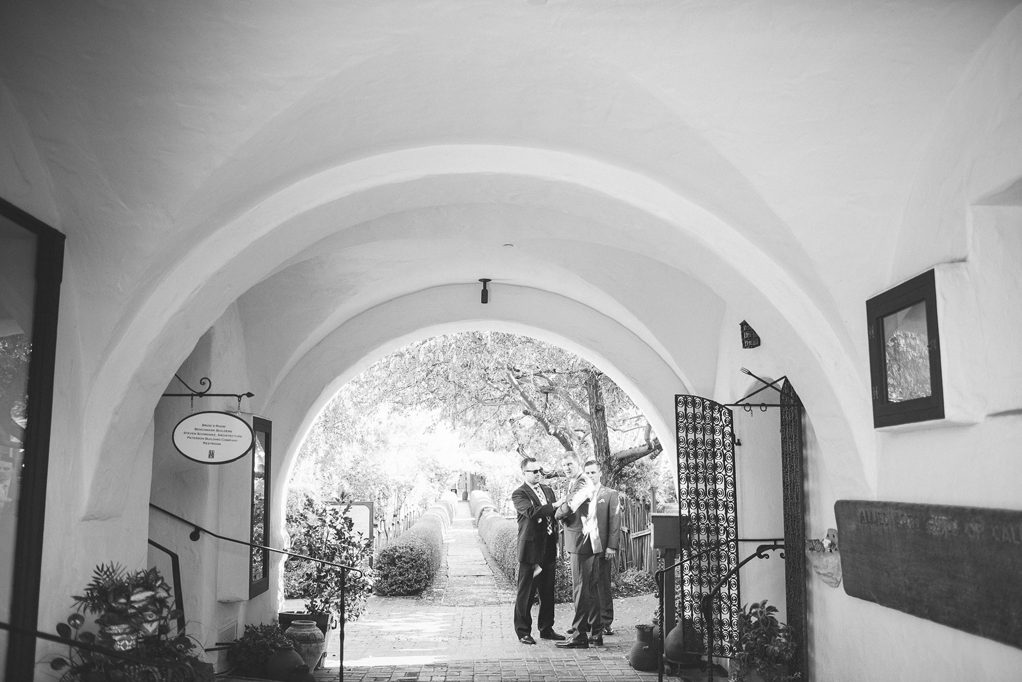 black and white image picture of groom greeting wedding guests as they arrive at their allied arts guild wedding venue