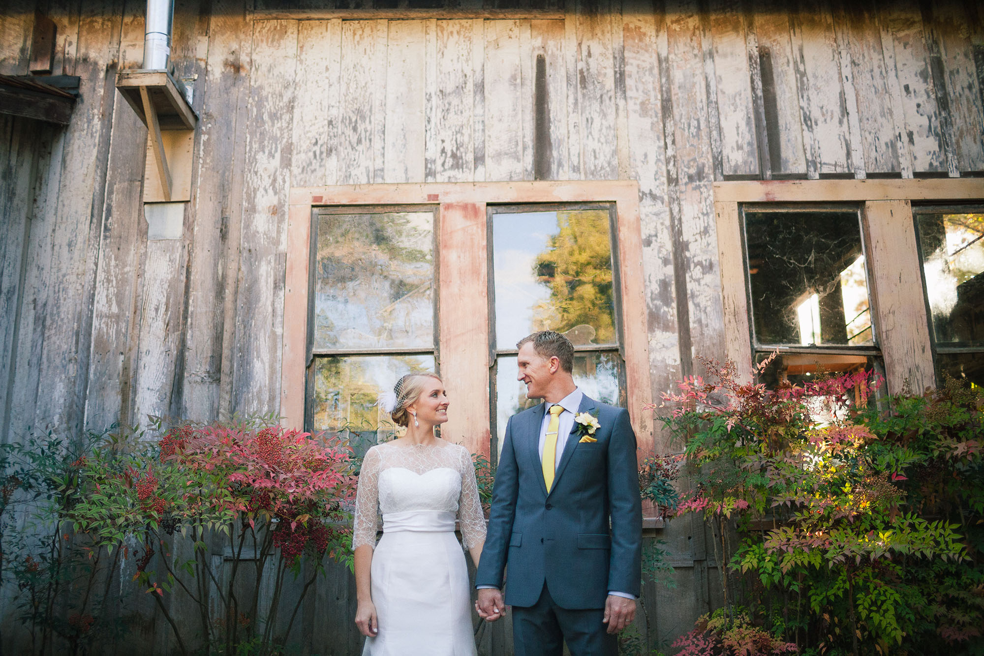 beautiful bride in her white wedding dress gown holds hands with her handsome husband in his tuxedo tux suit as they look at each other and smile in front of a rustic wood barn at their allied arts guild wedding venue