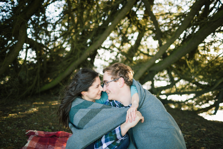 young engaged couple snuggles and hugs below the trees under a blanket to keep warm from the wind during their santa cruz engagement session