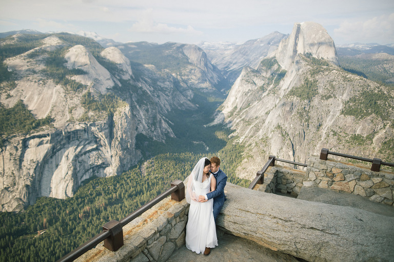happy newlyweds hug embrace at glacier point overlooking yosemite valley falls half dome at their yosemite wedding elopement